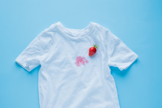 Dirty strawberry stain on fabric from accidents in everyday life. The concept of cleaning stains on clothes. Means of cleaning stains. Isolated on a blue background