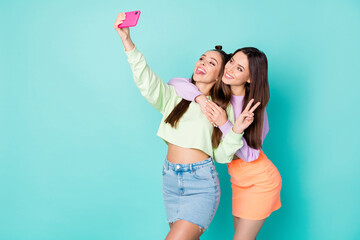 Keuken foto achterwand Texturen Photo of two pretty cheerful ladies best friends hold telephone take selfies showing v-sign symbol wear cropped sweaters naked belly short skirts isolated pastel teal color background
