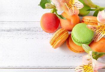 green, peach macaroon cookies, yellow Alstroemeria flowers, apricots on a white wooden background,