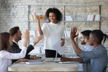 Smiling diverse business people raising hands, successful employees team with confident team leader voting at corporate meeting, colleagues making decision together, team building, staff training