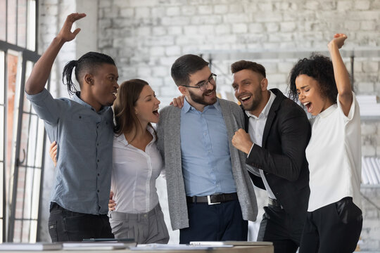 Excited diverse colleagues celebrating teamwork success, business achievement, hugging, laughing and screaming with joy, happy employees rejoicing victory in office together, having fun