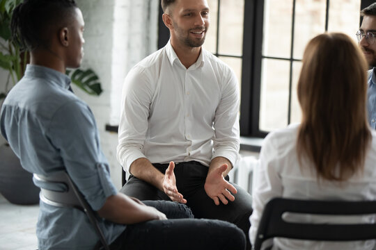 Smiling confident psychologist speaking at group therapy session, young man sharing problems with diverse people sitting in circle, listening to coach at meeting, mentor training staff