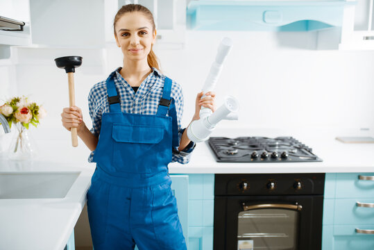 Female plumber in uniform holds plunger and pipe