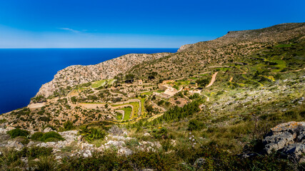 view over the old terraces and ruins of la trapa monastery nearby sant elm in springtime on mallorca, hiking route gr221 ruta de piedra en seco Wall mural