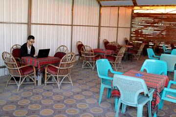A Palestinian graduate uses his laptop as he sits in a coffee shop amid COVID-19 crisis, in Gaza City