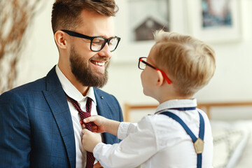 happy son helps father tie a necktie at home.