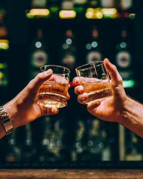 two guys clink glasses with whiskey at the bar