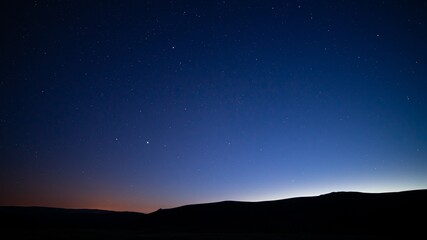 Silhouettes of hills under a starry sky at night - perfect for wallpapers and backgrounds