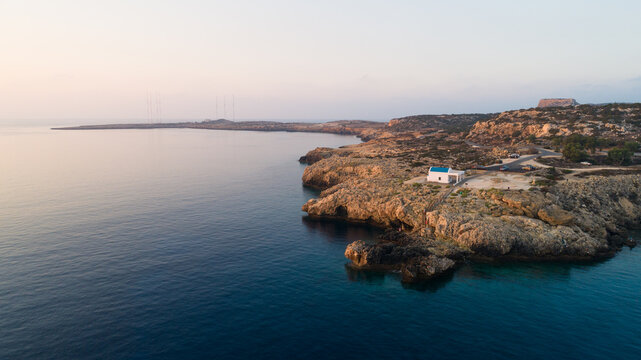 Aerial bird's eye view of coastline landmark white washed chapel Agioi Anargyroi, Cavo Greco Protaras, Famagusta, Cyprus from above. Tourist attraction cliff Ayioi Anargiroi church, caves at sunrise.