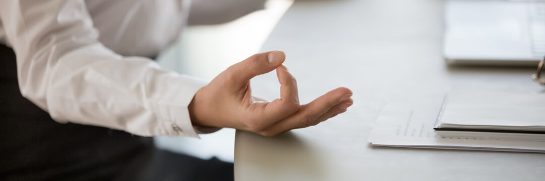 Calm business woman sitting at desk doing meditation practice close up view on folded fingers mudra gesture. No stress at workplace lifestyle concept. Horizontal photo banner for website header design