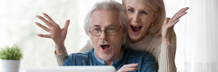 Keuken foto achterwand Texturen Horizontal photo 60s old couple happy husband overjoyed wife looking at laptop screen feel excited received fantastic news. Online lottery win, great commercial offer, banner for website header design