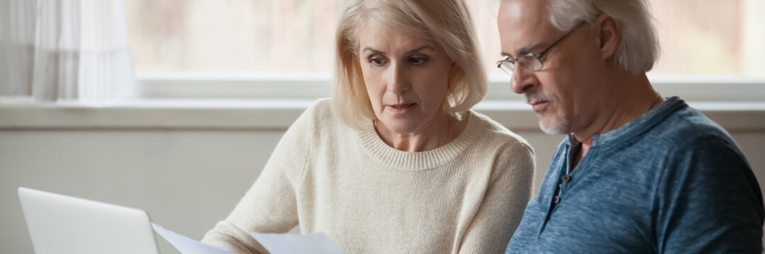 60s spouses serious couple read financial statement papers analyzing family expenses feels concerned. Bank debt, overspend, finance problems concept. Horizontal photo banner for website header design