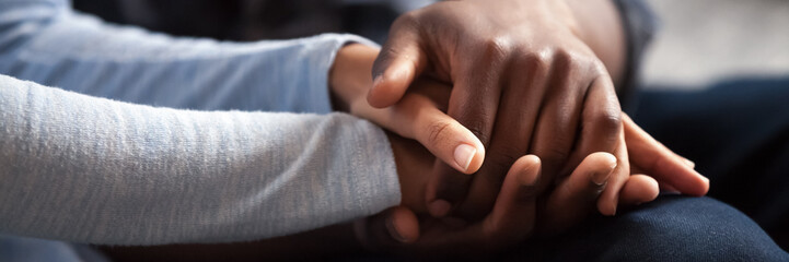 Close up photo african couple in love, woman man holding hands. Gesture of sincere feelings, compassion, apology, reliable friend, share pain or happiness. Horizontal banner for website header design