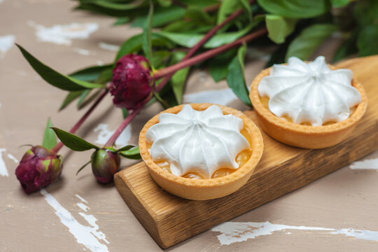 Lemon tart. Two cakes on a wooden plate and three peony flowers