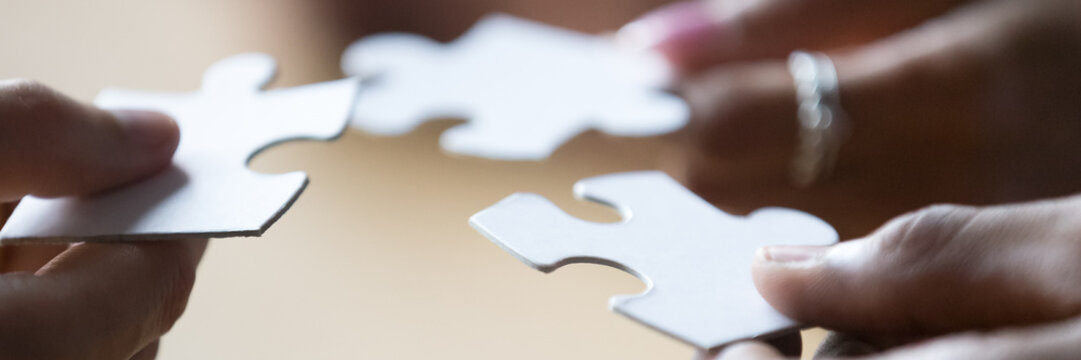 Close up photo hands of multi ethnic people hold diverse pieces of puzzle, team assembling jigsaw joining fragments, teamwork, search find solution concept. Horizontal banner for website header design