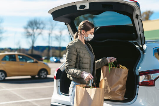 A young woman taking groceries from a supermarket from the car trunk. Social distancing: face mask, disposable gloves to prevent infection. Food shopping during coronavirus Covid-19 quarantine
