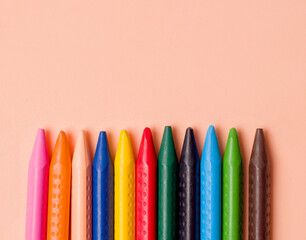 Crayons of different colors on a beige background. Copy space