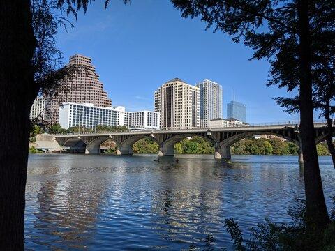 Austin TX bat bridge over river with buildings as back drop.