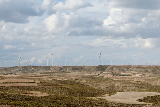 Agricultural fields and view from afar on cloudy skyline with windmills. Teruel Province, Aragon, Spain.