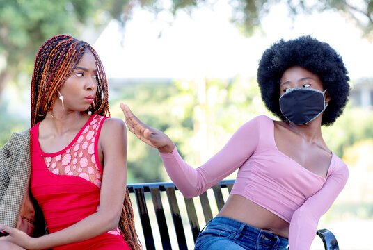 A girl wearing a face mask is trying to stay away from a person without a mask on the street. Masks are mandatory in many countries due to COVID-19 pandemic.