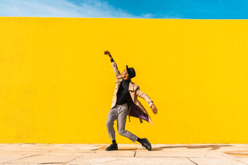 Young man dancing in front of yellow wall, taking selfies