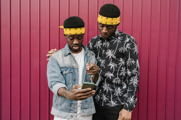 Portrait of two friends with headbands looking at cell phone Wall mural