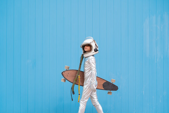 Kid dressed as an astronaut with longboard