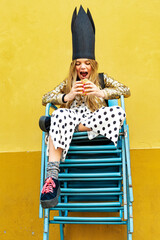 Portrait of girl wearing black crown sitting on stack of chairs eating Hamburger