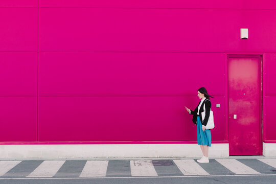 Young woman holding smartphone and waiting at a pink wall