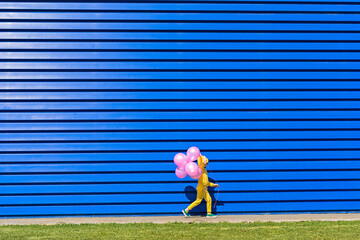 Little girl with pink balloons wearing yellow tracksuit walking in front of blue background