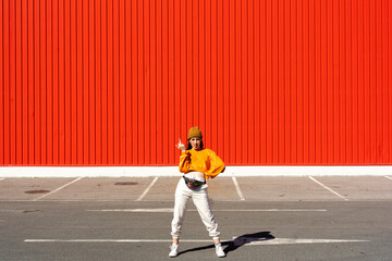 Young woman posing in front of a red wall Fototapete