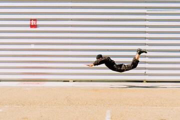 Man wearing black overall in the air in front of industrial building