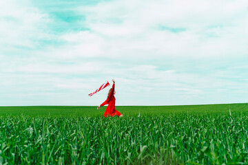 Woman wearing red dress running  on a field with windsock