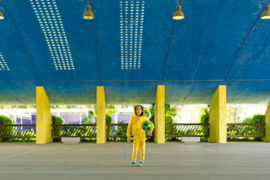 Portrait of girl in yellow tracksuit holding soccer ball outdoors