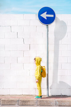 Girl standing on a traffic sign, direction left, in front of a white wall