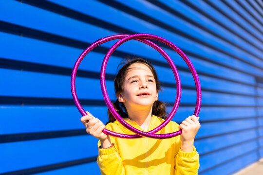 Portrait of little girl with gymnastic rings looking up