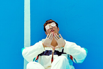 Portrait of woman wearing sunglasses and showing triangle with her hands