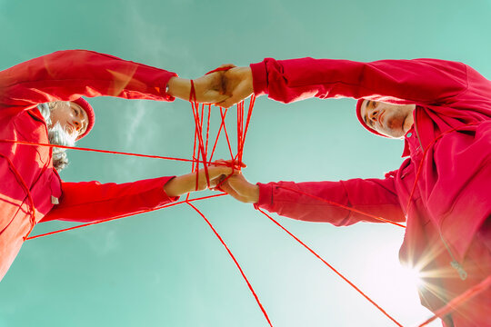 Directly below view of couple performing with red string against sky