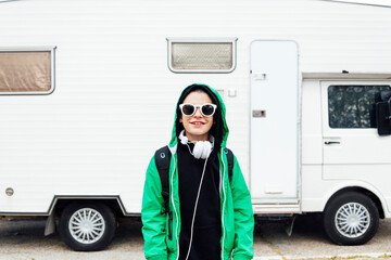 Portrait of boy with headphones wearing sunglasses standing in front of camper
