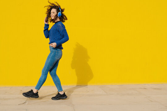 Smiling young woman with headphones and cell phone dancing in front of yellow background