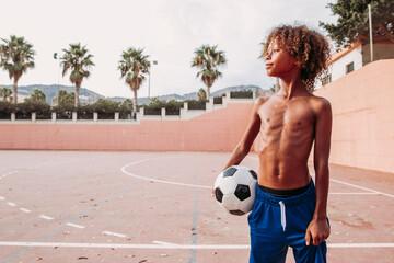 Boy holding a soccer ball standing on a soccer field