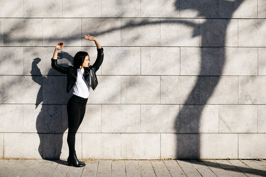 Young woman making shadows on a white wall with a shadow of a tree