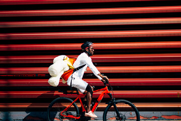 Bicycle courier delivering a teddy bear passing a red wall