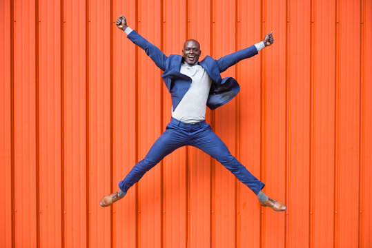Happy businessman jumping in the air in front of orange wall