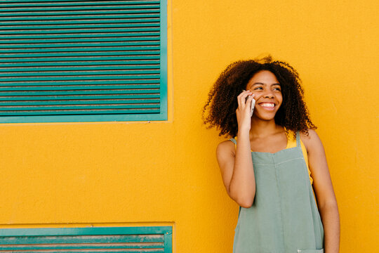 Portrait of happy young woman wearing overalls in front of yellow wall talking on the phone