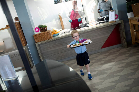 A child carries his food during lunch break at St Dunstan's College junior school as some schools re-open following the outbreak of the coronavirus disease (COVID-19) in London