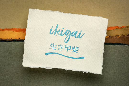 ikigai - Japanese philosophy and life style  - a reason for being or a reason to wake up  - handwriting on a handmade rag paper against abstract landscape