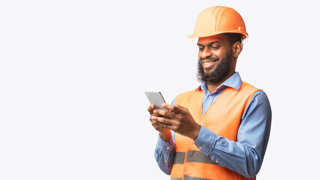 African Builder Worker Using Smartphone On White Studio Background, Panorama