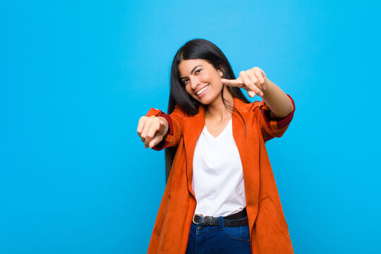 young pretty latin woman feeling happy and confident, pointing to camera with both hands and laughing, choosing you against flat wall
