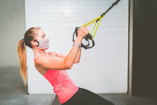 Girl training her arms with protective mask and straps Trx Fitness in the gym during quarantine time for pandemic covid19 - Woman doing push-ups trains the upper body chest shoulders pectoral triceps